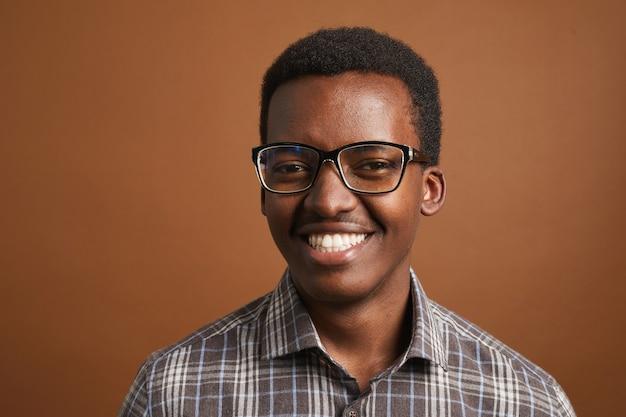 Portret van een jonge afro-amerikaanse man die lacht poseren op bruin