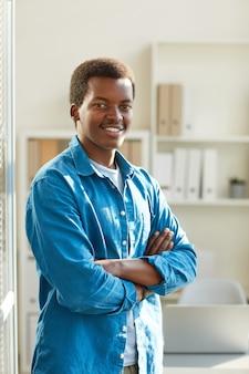 Portret van een jonge afro-amerikaanse man die lacht staan met armen gekruist in zonovergoten kantoor