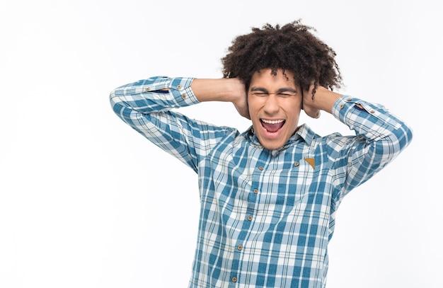 Portret van een jonge afro-amerikaanse man die zijn oren bedekt en schreeuwt geïsoleerd op een witte muur