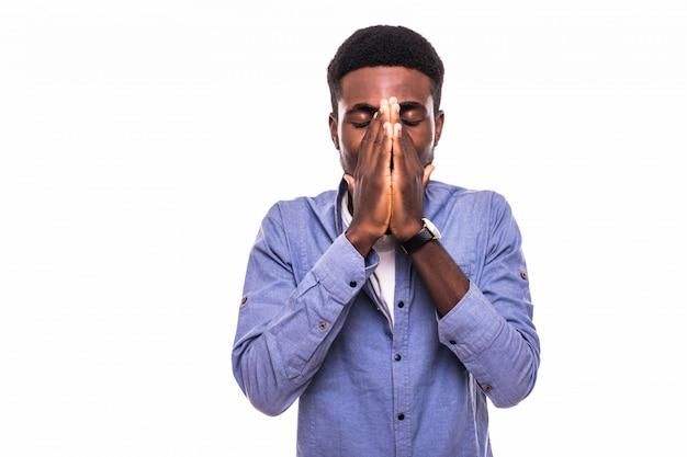 Portret van een jonge afro-amerikaanse man in geruit hemd die zijn mond met beide handen bedekt en met geschokte en schuldige uitdrukking kijkt alsof hij iets verkeerds heeft gedaan, staande aan een leeg bord