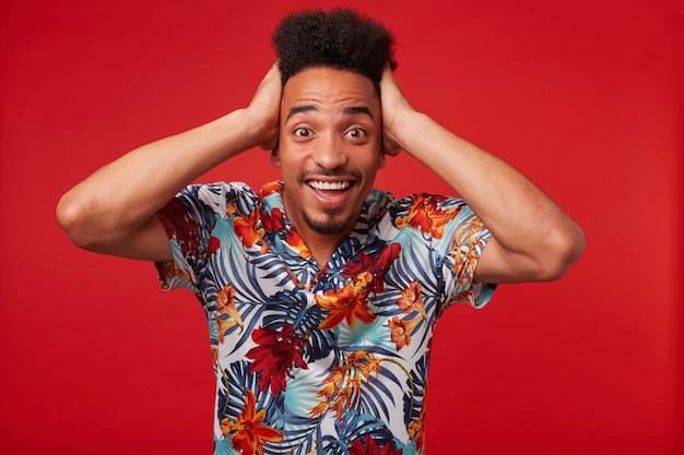 Portret van een jonge afro-amerikaanse man in hawaiiaans overhemd, kijkt verbaasd en gelukkig, staat op rode achtergrond en houdt zijn hoofd vast.