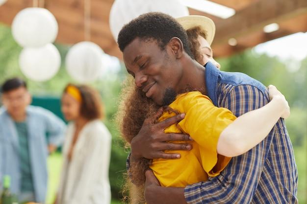 Portret van een jonge afro-amerikaanse man knuffelen vriend liefdevol terwijl ze elkaar begroeten op buiten feest in de zomer