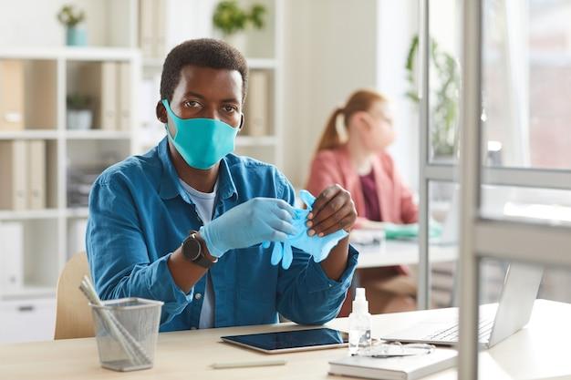 Portret van een jonge afro-amerikaanse man met masker en handschoenen werken aan een bureau in de cel bij post pandemie kantoor