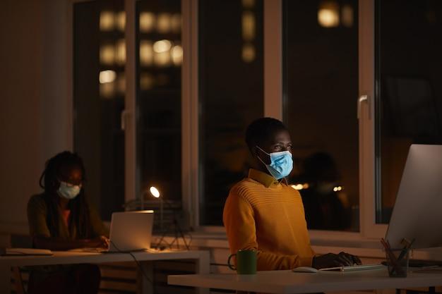 Portret van een jonge afro-amerikaanse man met masker in kantoor tijdens het gebruik van computer verlicht door scherm in het donker, kopieer ruimte