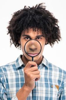 Portret van een jonge afro-amerikaanse man met vergrootglas geïsoleerd op een witte muur Premium Foto