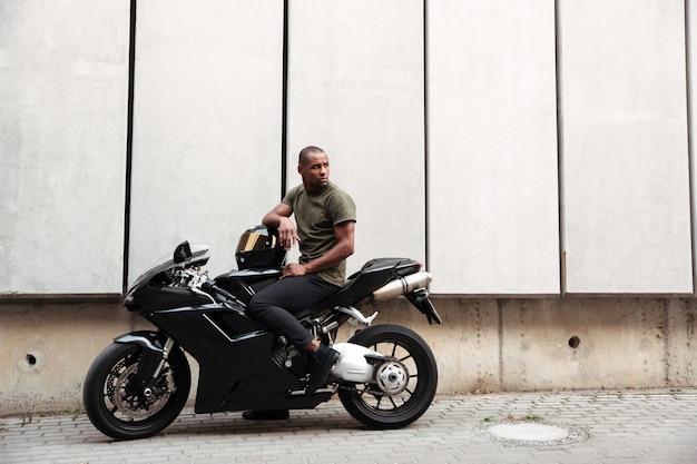 Portret van een jonge afro-amerikaanse man op een motorfiets