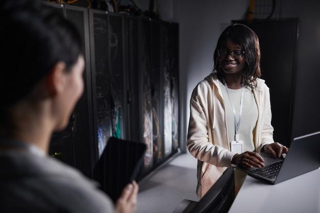 Portret van een jonge afro-amerikaanse netwerkingenieur die een laptop gebruikt terwijl hij in een donkere serverruimte werkt, kopieer ruimte