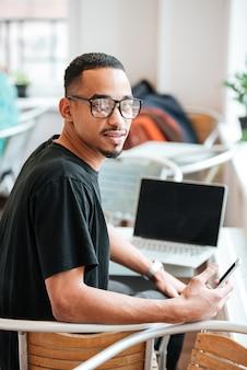Portret van een jonge afro-amerikaanse student met een bril die een mobiele telefoon vasthoudt en naar voren kijkt terwijl hij in een café zit