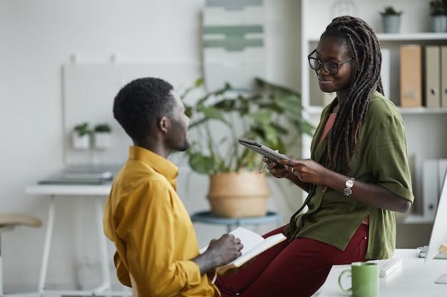 Portret van een jonge afro-amerikaanse vrouw chatten met mannelijke collega in kantoor en vrolijk glimlachen tijdens het bespreken van project, kopieer ruimte