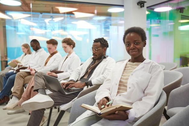 Portret van een jonge afro-amerikaanse vrouw die een laboratoriumjas draagt en naar de camera glimlacht terwijl ze in de rij zit met een multi-etnische groep mensen in het publiek tijdens een medisch seminar, kopieer ruimte