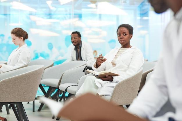 Portret van een jonge afro-amerikaanse vrouw die een laboratoriumjas draagt terwijl ze in het publiek zit en luistert naar een lezing over medicijnen op de universiteit of een coworkingcentrum, kopieer ruimte