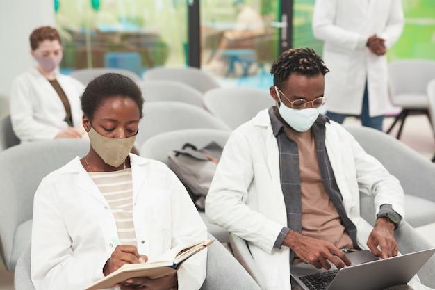 Portret van een jonge afro-amerikaanse vrouw die een masker en een laboratoriumjas draagt terwijl ze luistert naar een lezing over medicijnen op de universiteit of een coworkingcentrum, kopieer ruimte