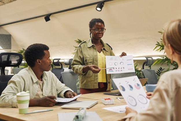 Portret van een jonge afro-amerikaanse vrouw die gegevensgrafiek houdt terwijl hij rapport van statistieken en prestaties geeft tijdens zakelijke bijeenkomst in modern kantoor, kopieer ruimte