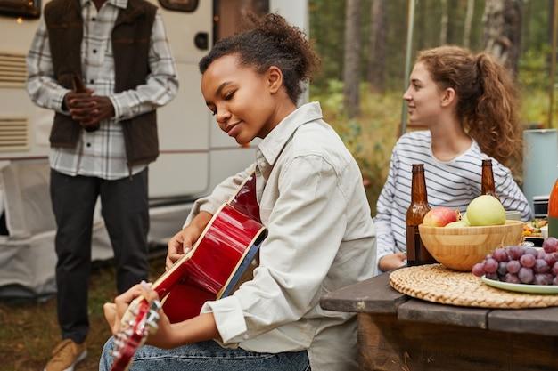 Portret van een jonge afro-amerikaanse vrouw die gitaar speelt terwijl ze geniet van buiten kamperen met vrienden