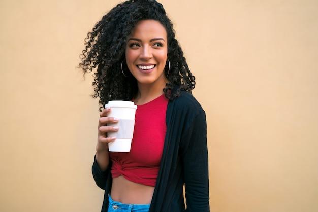 Portret van een jonge afro-amerikaanse vrouw die zelfverzekerd kijkt en poseren terwijl ze een kopje koffie vasthoudt tegen gele achtergrond.