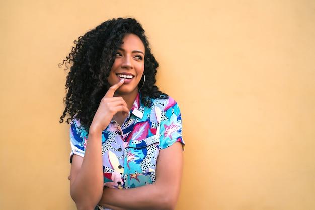 Portret van een jonge afro-amerikaanse vrouw die zelfverzekerd kijkt en tegen gele achtergrond stelt.