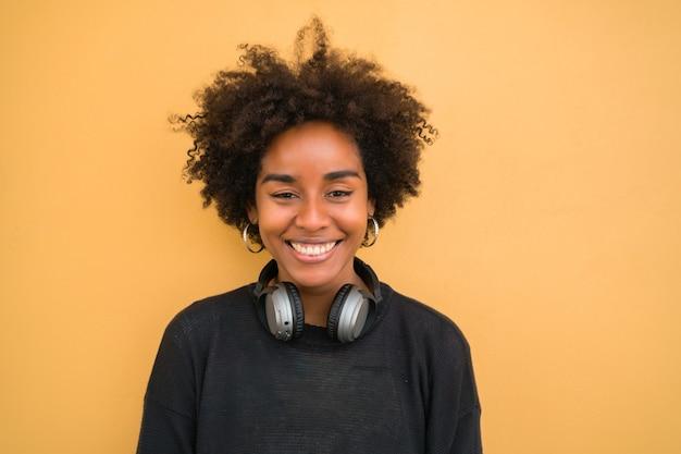 Portret van een jonge afro-amerikaanse vrouw die zelfverzekerd kijkt en zwarte hoofdtelefoons draagt tegen gele achtergrond.