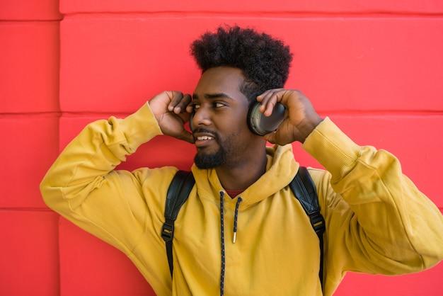 Portret van een jonge afro man luisteren naar muziek met een koptelefoon tegen rode ruimte. technologie concept.