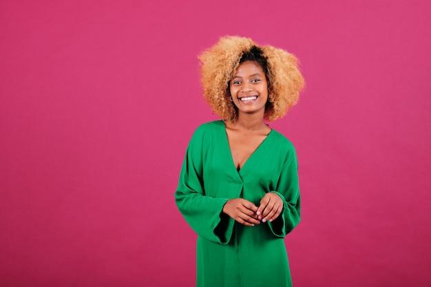 Portret van een jonge afro-vrouw in een groene jurk die lacht terwijl ze over een geïsoleerde achtergrond staat.