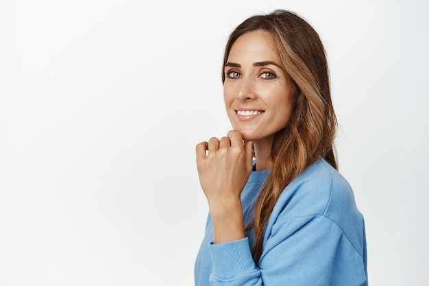 Portret van een jonge ambitieuze vrouw in blauwe blouse, draai het hoofd naar voren, glimlachend tevreden en zelfverzekerd