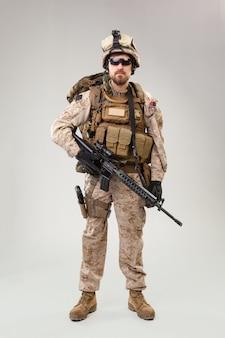 Portret van een jonge amerikaanse amerikaanse marine corps-soldaat over grijs