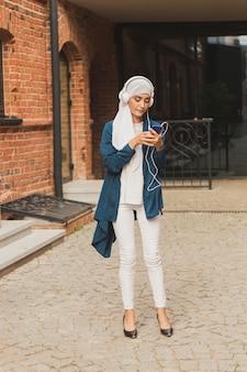 Portret van een jonge arabische moslimvrouw die muziek luistert met een koptelefoon en danst. feminisme, vrouwenonafhankelijkheid en vrije tijdsconcept.