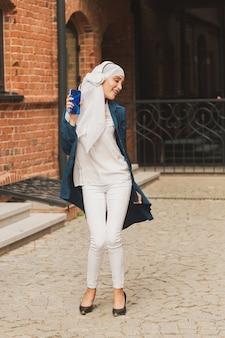 Portret van een jonge arabische moslimvrouw die muziek luistert met een koptelefoon en een dansende feminismevrouw