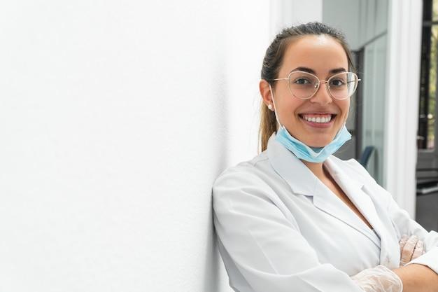Portret van een jonge arts die met haar neer masker glimlacht
