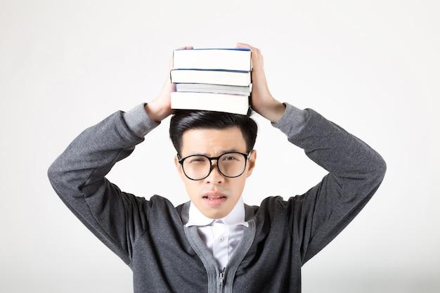 Portret van een jonge asiagraduate student met boeken over zijn hoofd. studio die op witte achtergrond is ontsproten. concept voor onderwijs