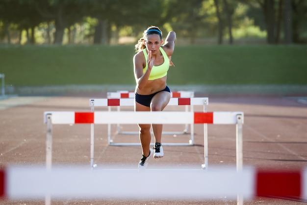 Portret van een jonge atleet die over een hindernis springt tijdens de training op het circuit.