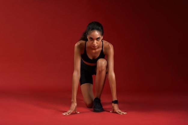 Portret van een jonge atleetvrouw in sportkleding die gaat rennen terwijl ze geïsoleerd over rood zit