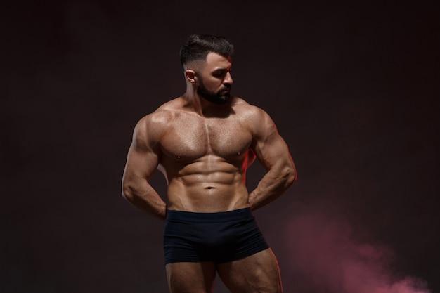 Portret van een jonge atletische man met een naakte torso die spieren toont
