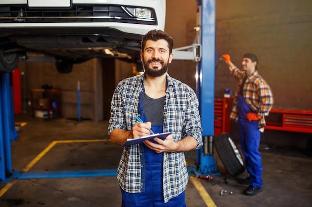 Portret van een jonge automonteur die op het klembord schrijft en naar de camera kijkt terwijl een andere specialist erachter werkt