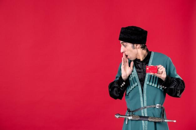 Portret van een jonge azerbeidzjaanse man in traditionele klederdracht met creditcard op rood