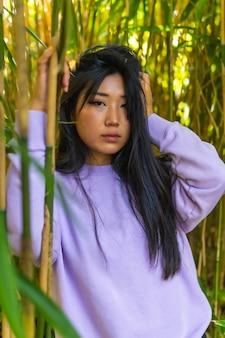 Portret van een jonge aziatische brunette in een park in prachtige bamboe met een roze trui.