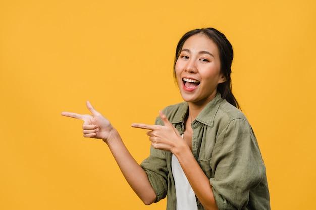 Portret van een jonge aziatische dame die lacht met een vrolijke uitdrukking, laat iets geweldigs zien op lege ruimte in een casual doek geïsoleerd over gele muur. gezichtsuitdrukking concept.