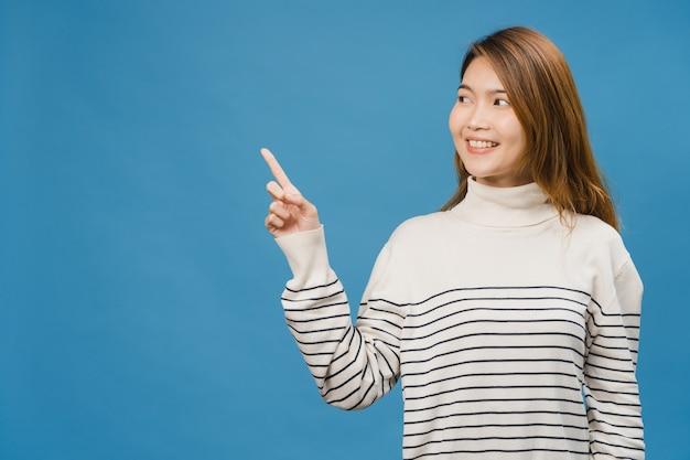 Portret van een jonge aziatische dame die lacht met een vrolijke uitdrukking, laat iets geweldigs zien op lege ruimte in vrijetijdskleding en geïsoleerd over een blauwe muur