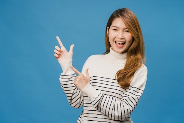 Portret van een jonge aziatische dame die lacht met een vrolijke uitdrukking, laat iets geweldigs zien op lege ruimte in vrijetijdskleding en kijkt naar de voorkant geïsoleerd over blauwe muur