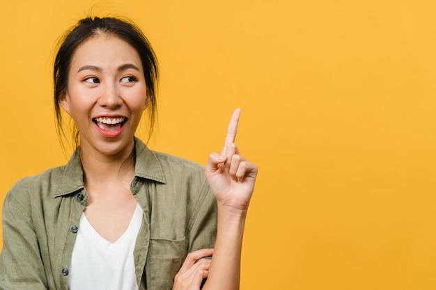Portret van een jonge aziatische dame die lacht met een vrolijke uitdrukking, laat iets geweldigs zien op lege ruimte in vrijetijdskleding en staat geïsoleerd over een gele muur. gezichtsuitdrukking concept.