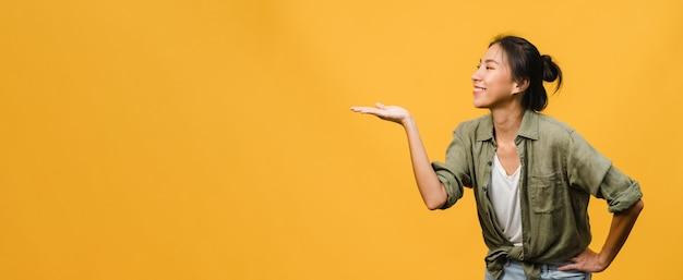 Portret van een jonge aziatische dame die lacht met een vrolijke uitdrukking, laat iets geweldigs zien op lege ruimte in vrijetijdskleding en staat geïsoleerd over een gele muur. panoramische banner met kopie ruimte.