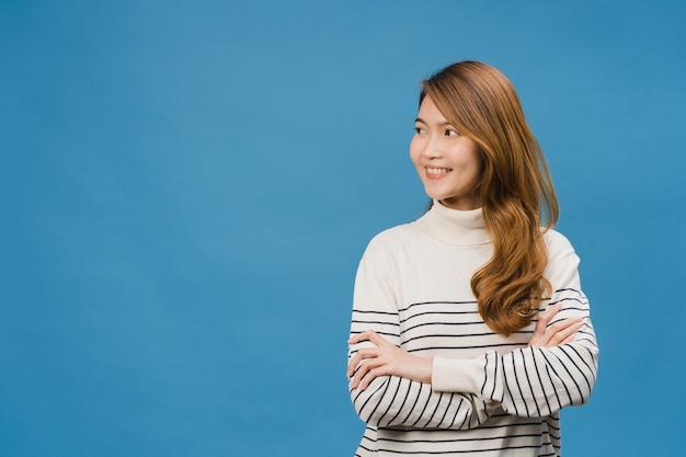 Portret van een jonge aziatische dame met positieve uitdrukking, armen gekruist, breed glimlachen, gekleed in vrijetijdskleding en kijkend naar de ruimte boven de blauwe muur