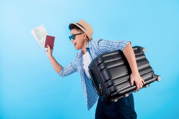 Portret van een jonge aziatische man die blij is, opgewonden met bagage, kaarten en paspoorten op een blauw