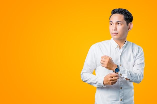 Portret van een jonge aziatische man die een horloge vasthoudt en zijwaarts kijkt