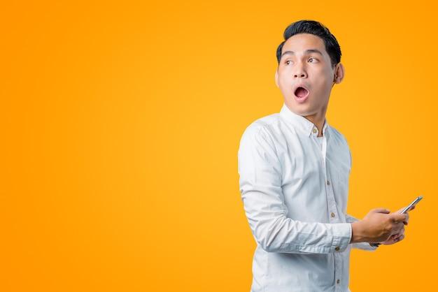 Portret van een jonge aziatische man die een smartphone vasthoudt en zijwaarts kijkt met een geschokte uitdrukking