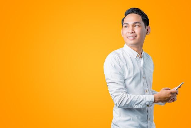 Portret van een jonge aziatische man die een smartphone vasthoudt en zijwaarts kijkt met een lachende uitdrukking