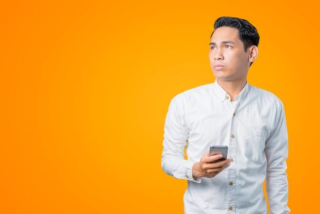 Portret van een jonge aziatische man die een smartphone vasthoudt en zijwaarts kijkt