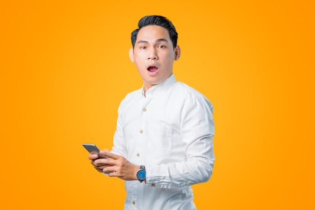 Portret van een jonge aziatische man die een smartphone vasthoudt met een geschokte uitdrukking