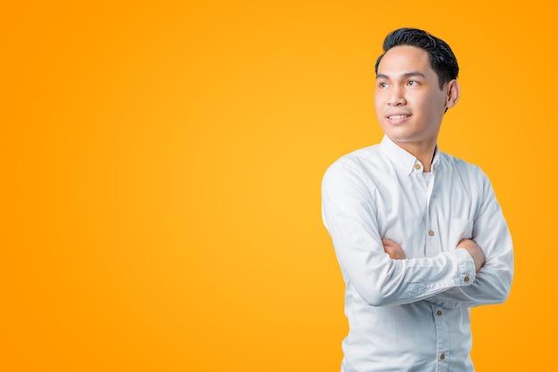 Portret van een jonge aziatische man die lacht en omhoog kijkt met gekruiste armen