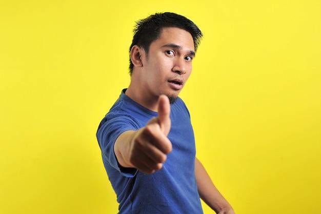 Portret van een jonge aziatische man die lacht met duimen omhoog voor de camera, geïsoleerd op geel