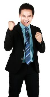 Portret van een jonge aziatische man die lacht terwijl hij een zwart pak draagt en zijn hand opsteekt om een gelukkige uitdrukking te maken die op een witte achtergrond wordt geïsoleerd. concept blij zakenmansucces voor het werken.